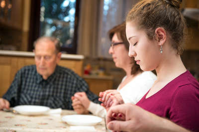 Catholic Family Praying at the dinner table