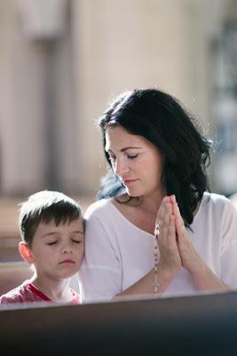 Mother praying with son in church